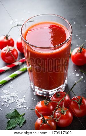 Fresh tomato juice and ingredients at dark slate table. Vertical.