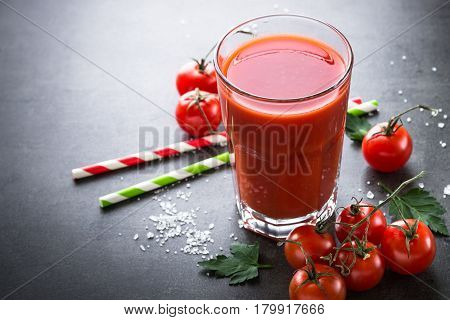 Fresh tomato juice with salt and ingredients at dark slate table.