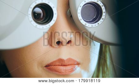 Ophthalmology concept - young woman checks the eyes on the modern equipment in the medical center, close up