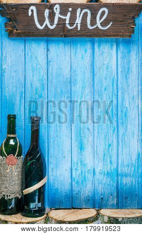 Various vintage wine bottles on blue painted wood with raw wood slices. Rustic signboard 'Wine' as title. Top view