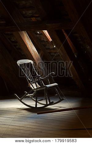 Old rocking chair on a dim attic