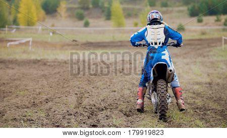 Motocross racer start riding his dirt Cross MX bike - rear view, telephoto