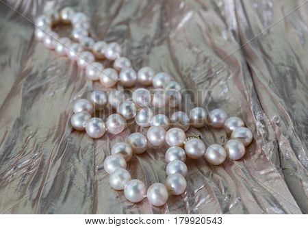 Pink pearl necklace on dusty rose pink pleated satin background close up
