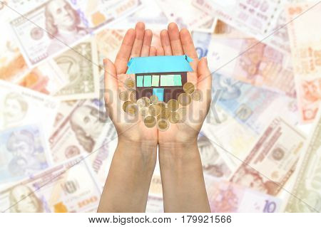 Hands holding coins and small house on background of banknotes. Concept on the topic of Finance, purchase and sale of housing