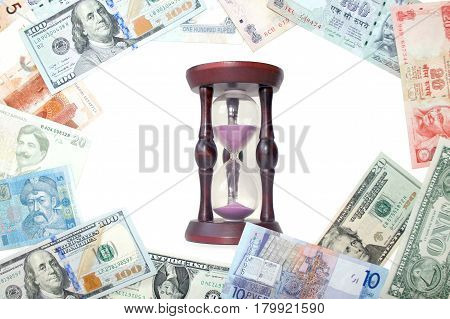 Hourglass with purple sand on the background of banknotes of different countries. Concept on the topic of Finance and time.