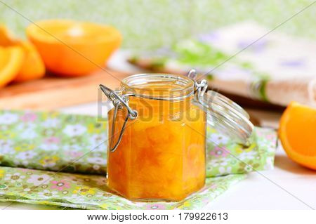 Tasty orange jam. Sweet orange jam in a glass jar, textile, napkin, orange slices on a wooden board. Simple citrus dessert idea