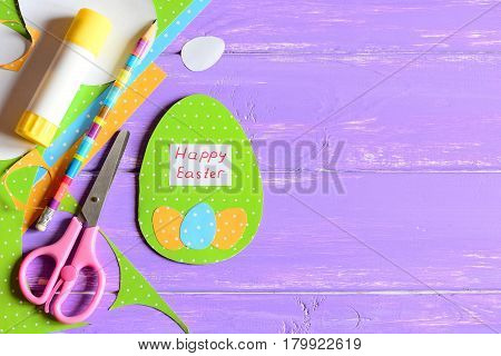 Happy Easter greeting card, stationery on lilac wooden background with copy space for text. Adorable greeting card made in form of egg with wishes Happy Easter. Colorful Easter background