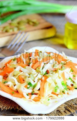Homemade coleslaw on a plate. Coleslaw salad with carrots, pumpkin seeds, greens and dressed with lemon juice and olive oil. Easy and quick diet salad. Vertical photo