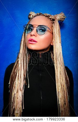 attractive young  blonde woman with  african braids in black pullover  on blue background