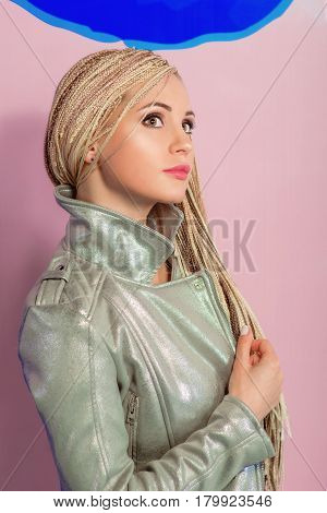 Beautiful young attractive stylish woman with african plaits on pattern of blue lips background