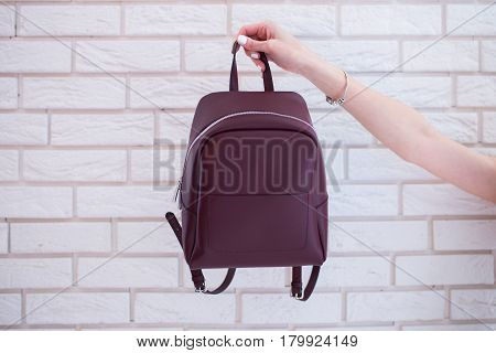 Women's backpack of marsala color in hand on loft background