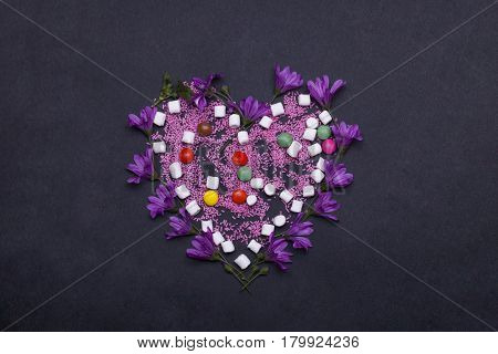 colorful tasty marshmallow zephyr and dragee sprinkles sweets violet spring flowers in valentines day heart shape on grey background copy space