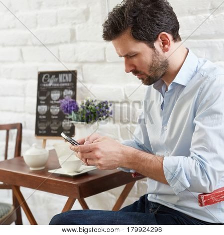 Man sitting at coffee table, using mobilephone.