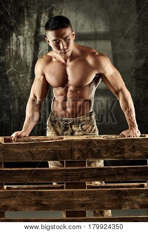 Determined asian male bodybuilder standing behind pallet, looking down.