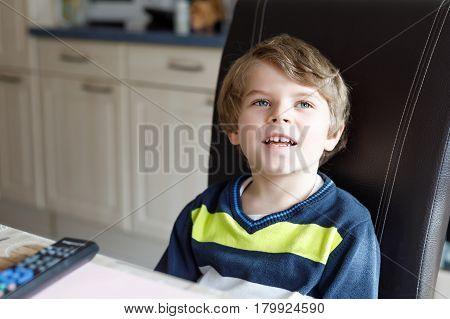 Cute little blond preschool kid boy watching tv. Happy child oprerating with remote control and choosing cartoons or education program. Television as not active leisure for children.