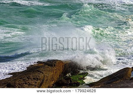 Waves crashing against beach rocks during storm
