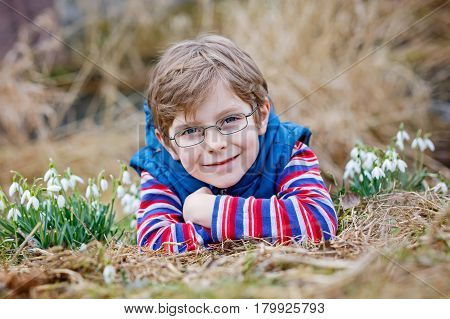 Cute blond preschool kid boy with glasses discovering first spring flowers, beautiful snowdrops. Active happy child in colorful clothes on meadow. Child as model for eye wear and optician