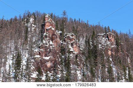 Reddish weathered rocks in Southern Yakutia Russia in winter