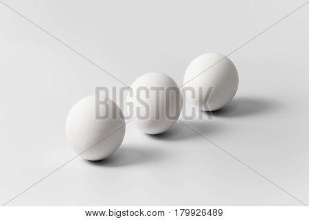 Three white eggs arranged diagonally on a white background close-up