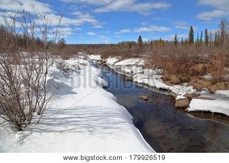 Spring landscape with a melted stream in South Yakutia Russia