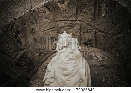 Statue of virgin Mary with stoned background. White stone statue of Saint Mary. Virgin Mary and baby Jesus. Jesus Christ and saint Mary sculpture.