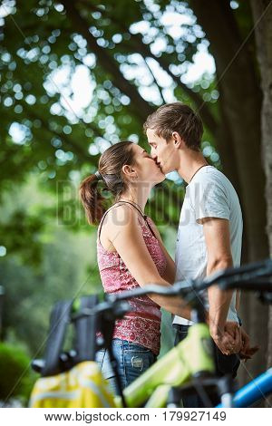 Young people, couple with bicycles in the park. A loving couple on a date on a summer evening. The guy with the girl hugs and kisses. Youth, first feelings, first love, first dates