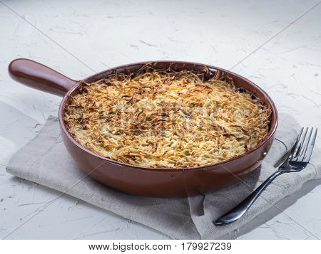 Close up view of appetizing potato casserole with fish, eggs and cream. Potato casserole in serving baking pan on white concrete background