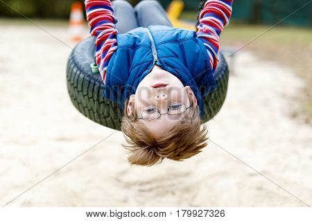 Funny kid boy having fun with chain swing on outdoor playground. child swinging on warm sunny spring or autumn day. Active leisure with kids. Boy wearing casual colorful clothes, eye glasses
