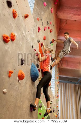 fitness, extreme sport, bouldering, people and healthy lifestyle concept - happy man and woman exercising at indoor climbing gym