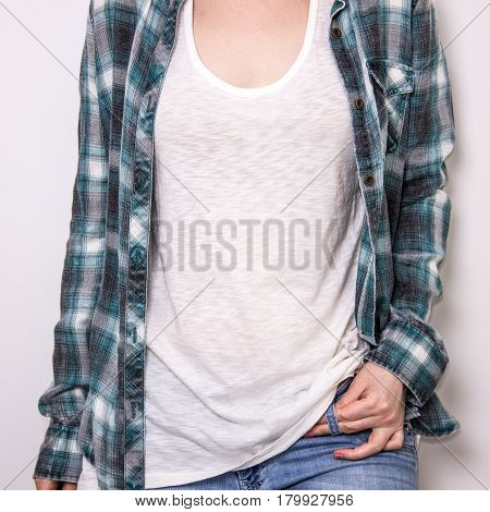 Cropped image of young hipster girl wearing blank white t-shirt under the plaid shirt and blue jeans mockup.