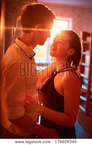 Young people hugging in the apartment in the evening in the rays of the sunset. A loving couple on a date on a summer evening. The guy with the girl hugs and kisses. Youth, first feelings, first love, first dates. faces close up. Sun flares in the frame a
