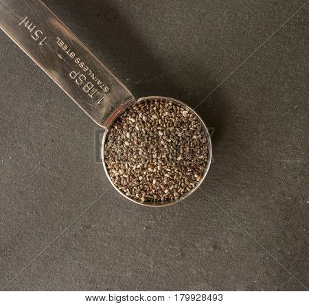 Chia seeds on spoon close up on dark background