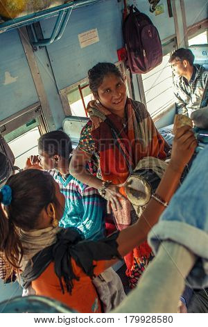 Unidentified women musician performers singing songs and playing drums for passengers inside Indian Railway local train on December 2012 in India. Indian Railways carries about 7, 500 million passengers annually.