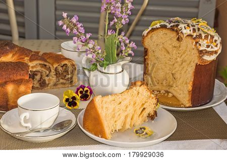 Typical italian flavorous home baked cakes for Easter: La Gubana with sophisticated stuffing and Panettone with candied flowers on the table covered for tea time. Horizontal close up. Main colors: white gray yellow brown.