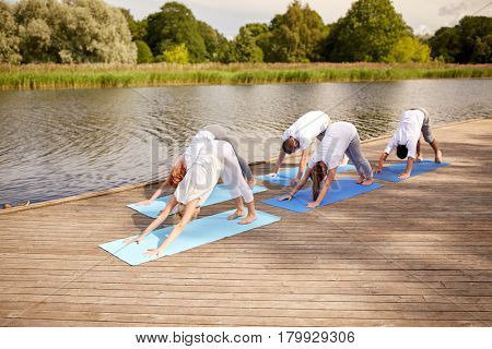 fitness, sport, yoga and healthy lifestyle concept - group of people making downward facing dog pose on river or lake berth