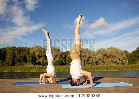 fitness, sport, yoga, people and healthy lifestyle concept - couple making headstand pose on mat on river or lake berth