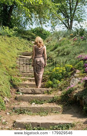 Slim young blonde girl in a brown sundress climbs up the stairs in the park. Summertime.