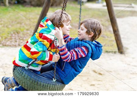 Two little kid boys having fun with chain swing on outdoor playground. Children, best friends and siblings swinging on warm sunny spring or autumn day. Active leisure with kids. Casual boy fashion