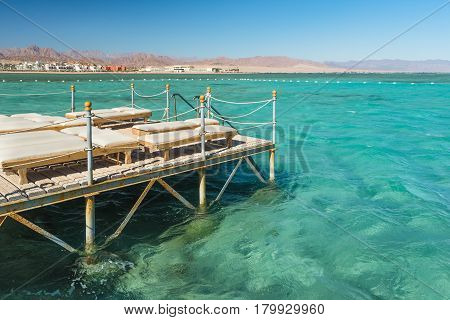 Pier with chaise longues in the sea in resort. Summer vacation. View at a clear sea with turquoise water. Summer vacation at a sea coastline in an exotic country. Staircase to the water for swimming.
