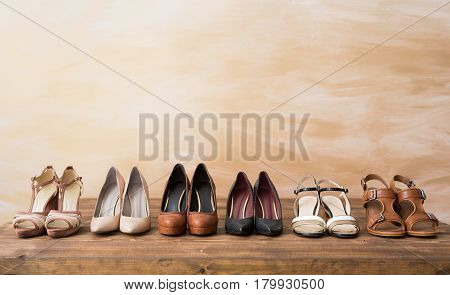 Organized woman's shoes on wooden floor background