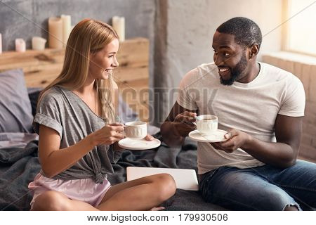 Delight inside of us. Positive lovely international couple sitting in the bedroom and drinking tea while enjoying weekend and expressing positivity
