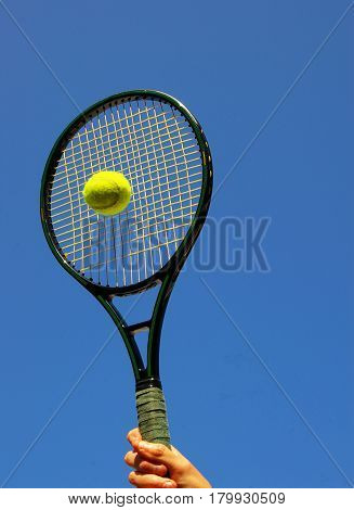 Person hitting a tennis ball with blue sky