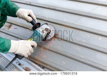 hands in  rag gloves grinds corrugated steel structure for painting primer anti rust. Red sparks from  wheel.
