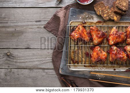 Dinner table with homemade chicken wings and cranberry sauce. Top view with copy space. Rustic style