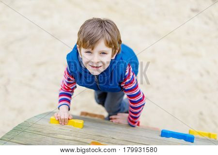 Happy blond kid boy having fun and climbing on outdoor playground. Funny joyful child smiling and romping on slide. Summer, spring and autumn leisure for active kids. Boy in colorful fashion clothes