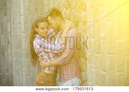 Toned image. Happy young couple hugging near brick wall. Young people in summer clothes in love with and enjoying their time.