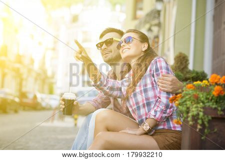 Young man and woman together sitting on stairs of fashionable shop. Gilr showing to her boy-friend something in the sky. Toned image.