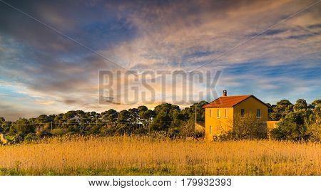 Orange farmhouse in Sardinian countryside in Italy