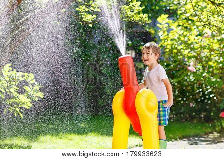 Active preschool kid boy  playing and splashing with a garden hose on hot and sunny summer day. Child having fun outdoors. Funny outdoors leisure wth water for children.
