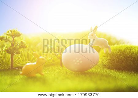 Decorated Easter Eggs With Easter Rabbit On Grass Over Sky Background.